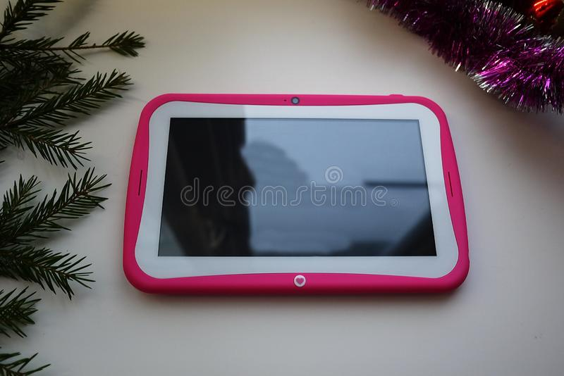 Tablet in the hands of a child. Tablet with a bright cover stock photography