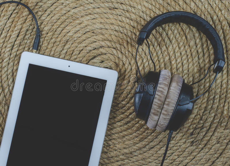 Tablet headphone music on a jute rope background. Tablet and headphone music on a jute rope background stock photos