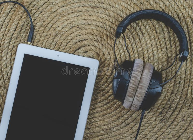 Tablet and headphone music on jute rope background. Tablet and headphone music on a jute rope background stock photos