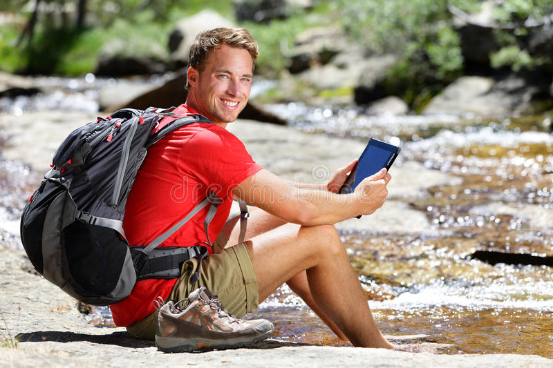 Tablet hiking man reading ebook or map in nature stock photos