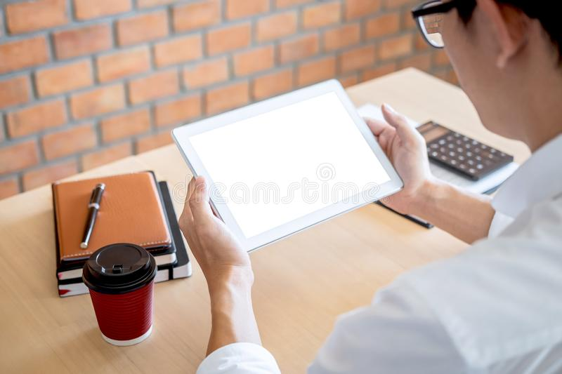 Tablet horizontal screen mockup, Image of Young man working in front of the digital tablet switching on to start his work, looking royalty free stock images