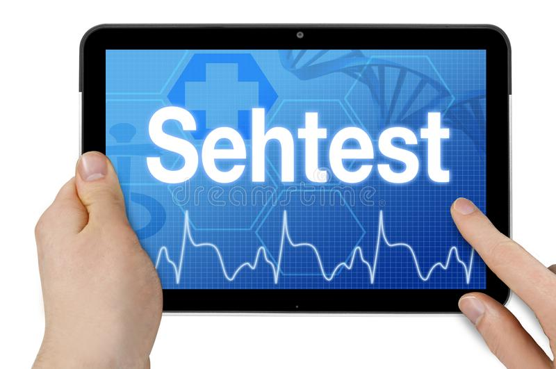 Tablet with medical device and the german word for eye test - sehtest royalty free stock photos