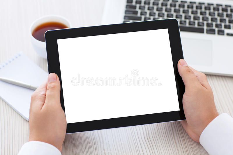 Tablet with isolated screen in male hands over the table royalty free stock photo