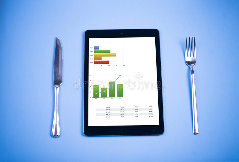 Tablet, knife, fork, and food with graphic colors royalty free stock photography
