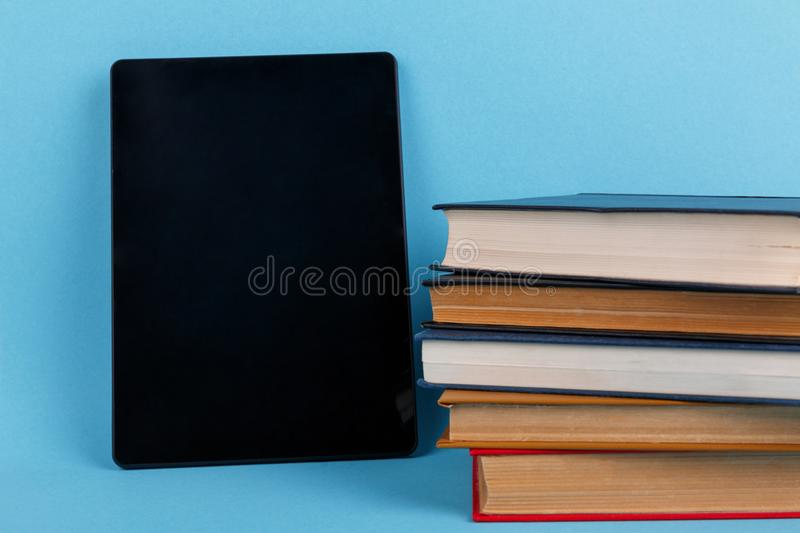 A tablet is located near a pile of books. The concept of knowledge. On a blue background. A black modern tablet is located near a pile of various books. The stock image