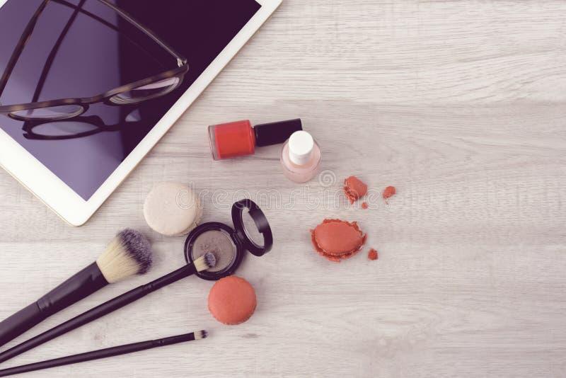 Tablet, Make-upkosmetik, Bürsten, Gläser und geschmackvolle macarons auf weißem hölzernem Hintergrund, Draufsicht, Kopienraum lizenzfreie stockfotografie