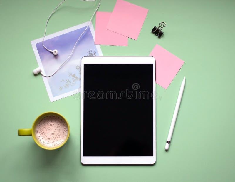 Tablet met een naald op een groene achtergrond Een Kop van koffie, hoofdtelefoons, foto stock afbeeldingen
