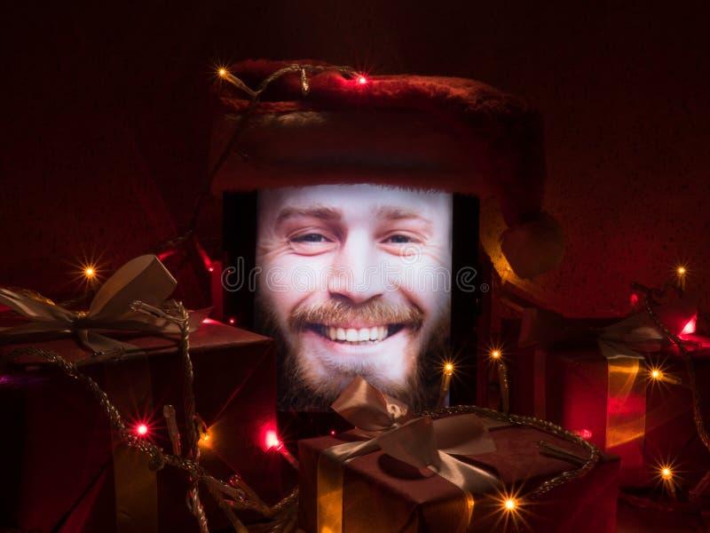 Tablet met gelukkig gebaard mannetje op het scherm en santa GLB op het met Kerstmis rond giften en slinger van bollen royalty-vrije stock afbeeldingen
