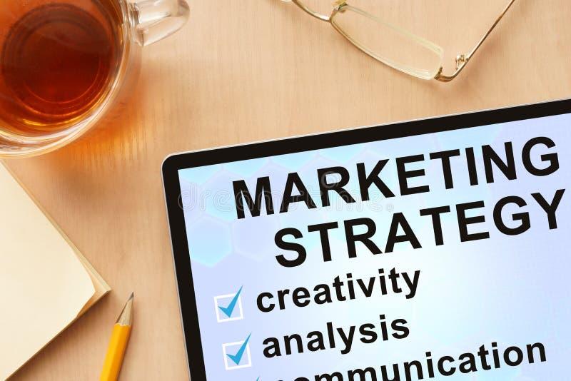 Tablet met woorden die strategie op de markt brengen stock fotografie
