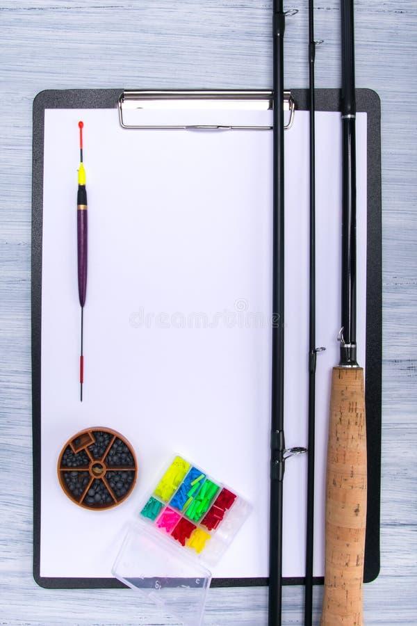 Tablet mit einem weißen Blatt Papier, auf einer hellgrauen Tabelle, mit Einzelteilen für die Fischerei, Angelrute, Flöße, Senkble lizenzfreies stockfoto