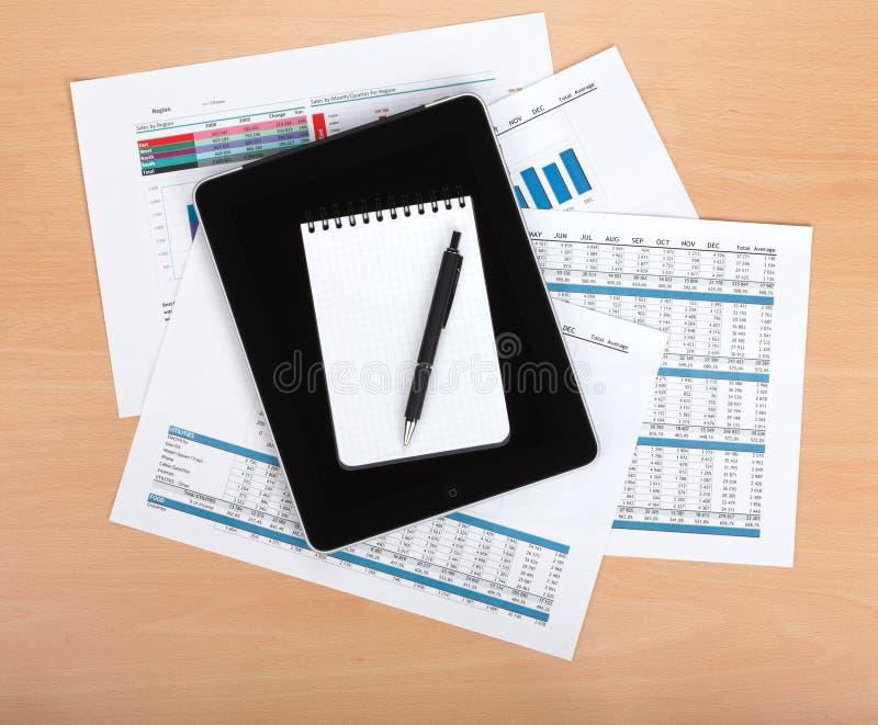 Tablet mit leerem Bildschirm über Papieren mit Zahlen und Diagrammen stockbilder