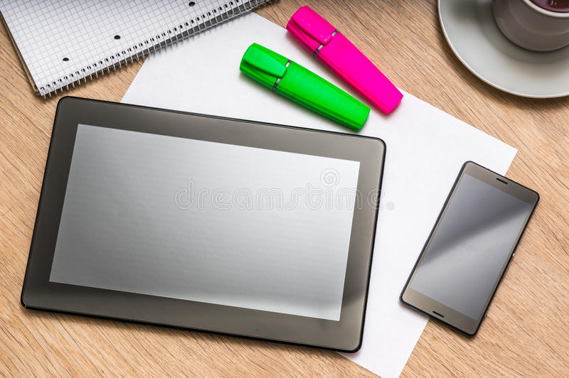 Tablet, mobile phone, markers, note and cup of coffee on table. Workplace with digital tablet, mobile phone, paper, coloured markers, note and cup of coffee on royalty free stock photo