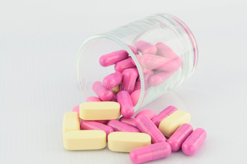 Tablet- och rosa färgkapsel royaltyfri foto