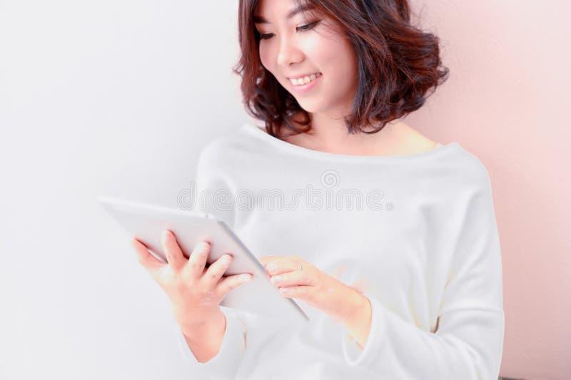 Tablet pc asiático novo do uso da mulher do sorriso fotografia de stock royalty free