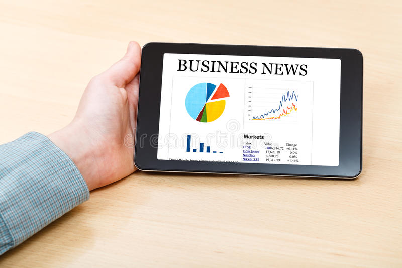 Tablet PC with business news on screen at desk. Businessman hand hold tablet PC with business news on screen at office desk royalty free stock images