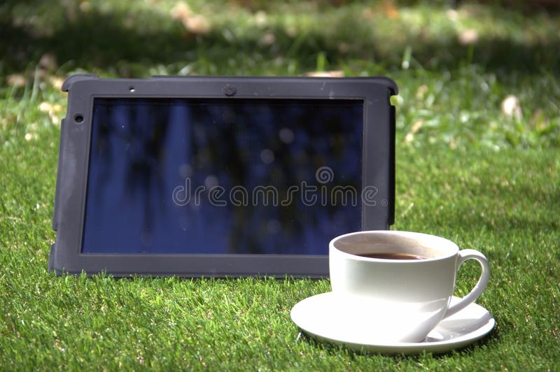 Tablet Pc And A Cup Of Coffee On The Grass Stock Image