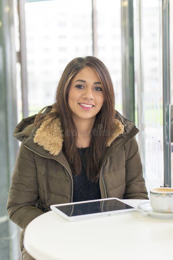 Tablet pc de sorriso bonito do portátil da mulher na cafetaria fotografia de stock
