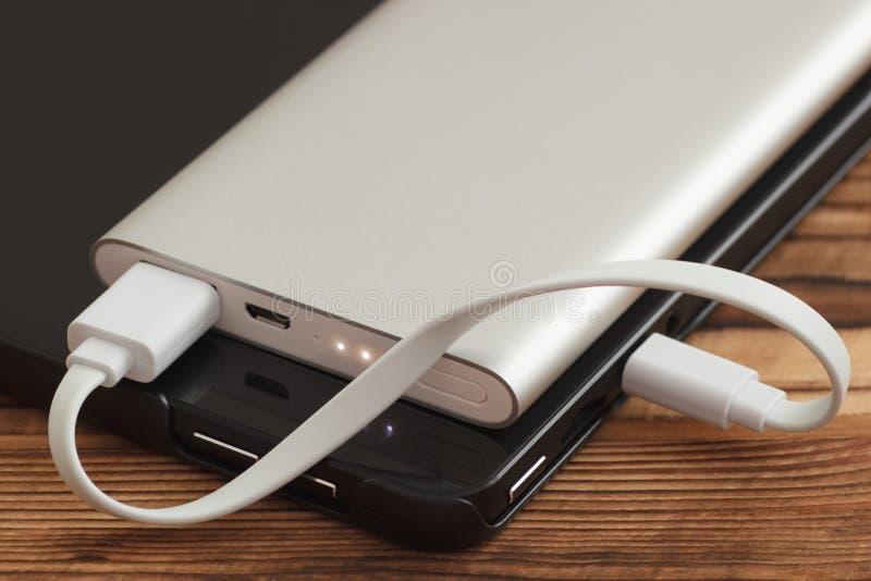 Tablet-PC, der mit Aussenbord-Stromversorgungsanlage Bank auflädt stockfotos