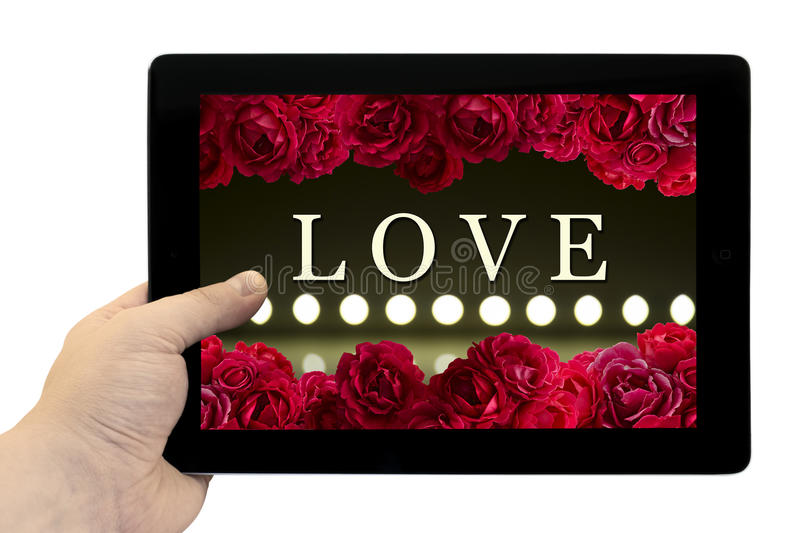 Tablet PC in hand with frame with love card with bush of red rose flowers and play of light on defocusing blur led lamps. Background on screen isolated on white royalty free stock image