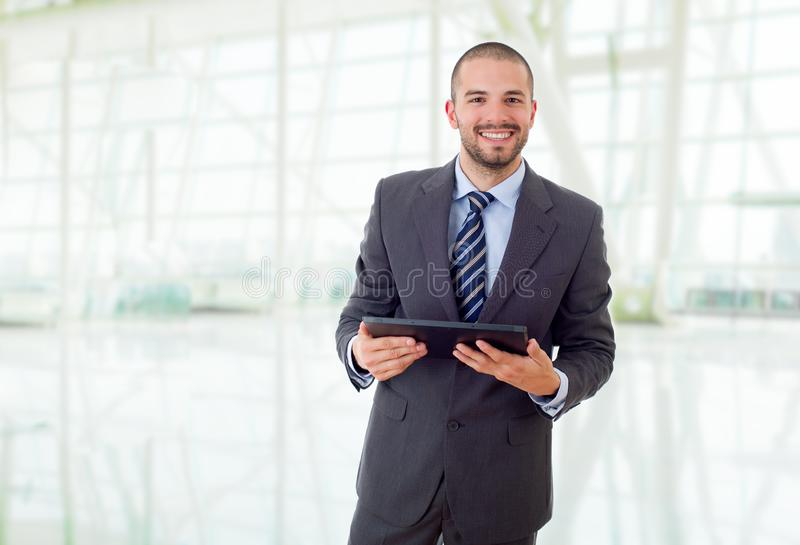 Tablet pc. Happy businessman with a tablet pc, at the office stock photography