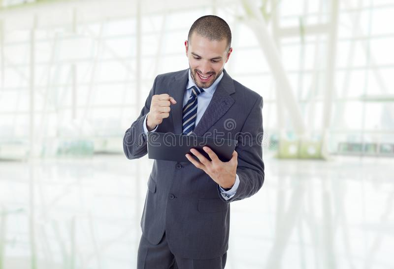 Tablet pc. Happy businessman working with a tablet pc, at the office royalty free stock photo