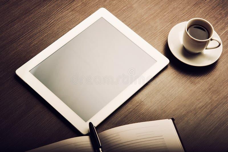 Tablet PC:n, och ett kaffe och en anteckningsbok med skrivar på kontorsskrivbordet royaltyfri foto