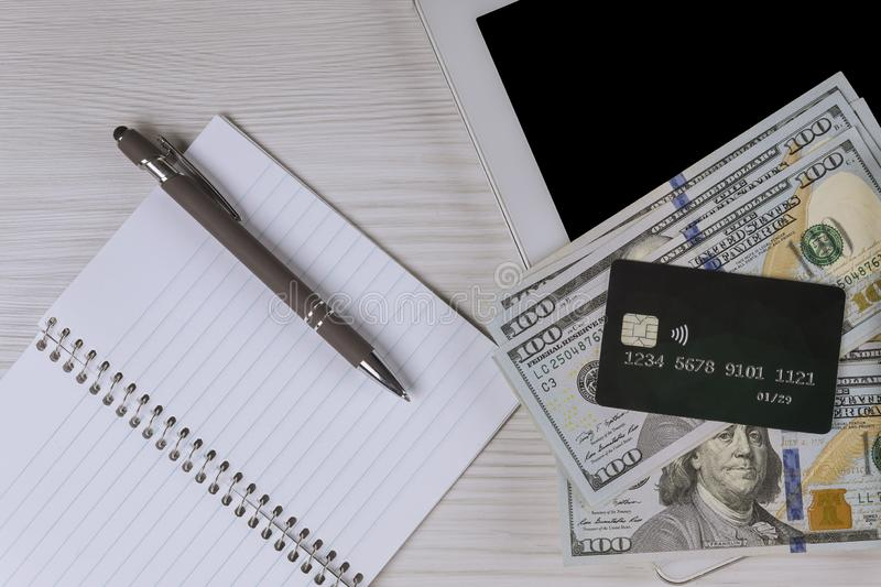 Tablet pc with pen, credit card in dollars money on wood table top view stock photography
