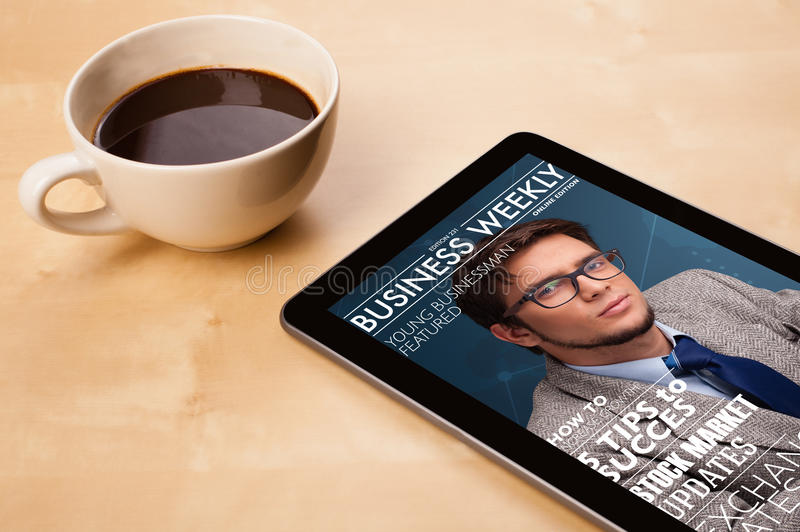 Tablet pc showing magazine on screen with a cup of coffee on a d. Workplace with tablet pc showing magazine cover and a cup of coffee on a wooden work table stock photo