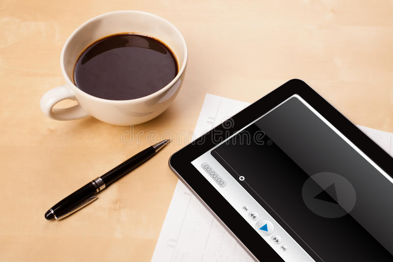 Tablet pc showing media player on screen with a cup of coffee on. Workplace with tablet pc showing media player and a cup of coffee on a wooden work table close royalty free stock images