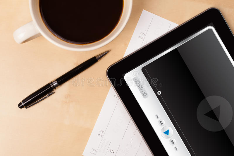Tablet pc showing media player on screen with a cup of coffee on. Workplace with tablet pc showing media player and a cup of coffee on a wooden work table close royalty free stock photography
