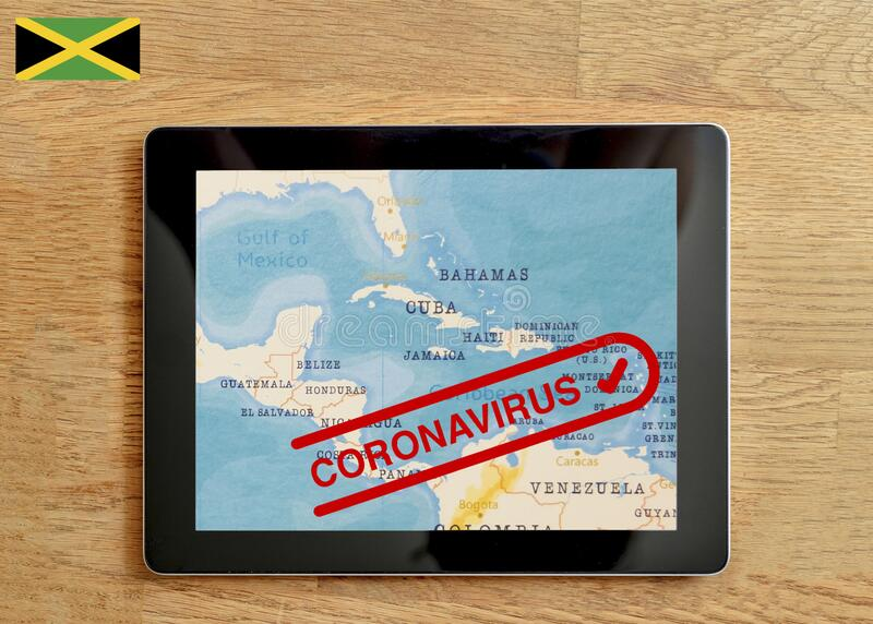 A Tablet PC which is displayed with map of Jamaica and Coronavirus text on the wooden table. 