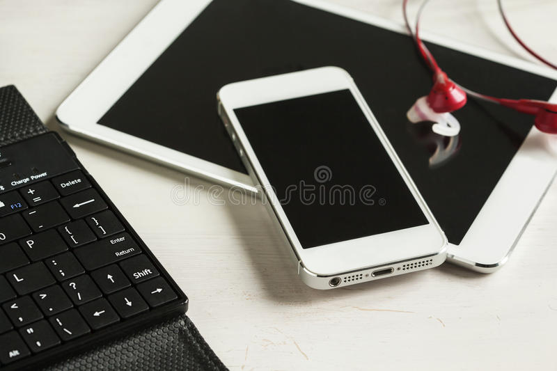 Tablet, phone with headphones close up and keyboard royalty free stock photos