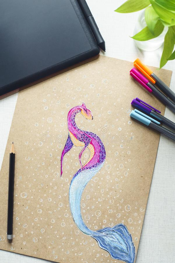 Water dragon. Drawing courses on the tablet. Tablet and picture of water dragon of pink and purple colors. Gepard and fish. Flat lay. Creative process. Drawing royalty free stock photos