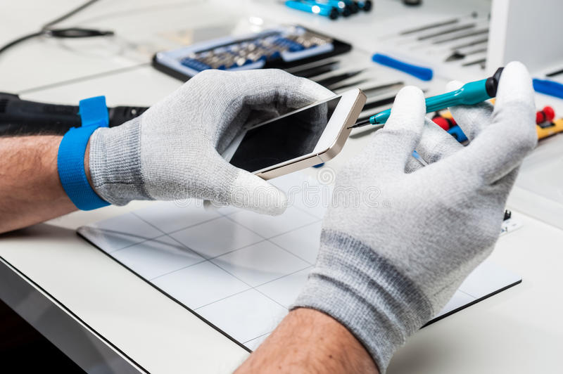 Tablet, pod repair. Technician hands repairing a used tablet, pod with broken screen royalty free stock photo