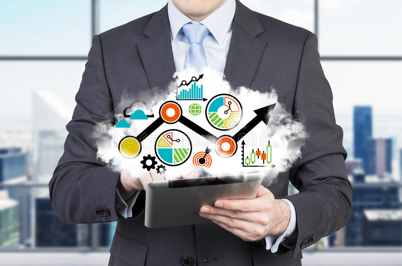 Tablet's projection of the business strategy flowchart. Businessman is holding a tablet. Panoramic office in New York city stock photos