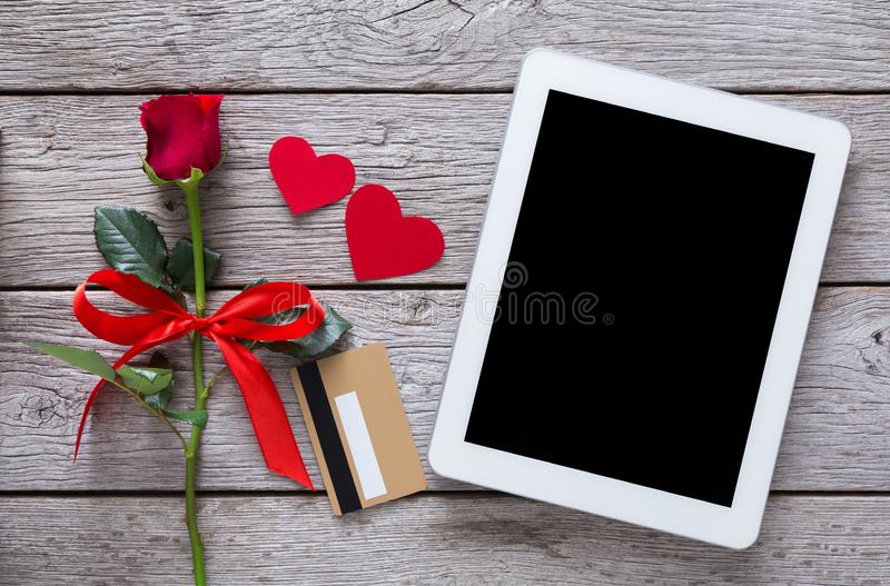Online shopping holiday background, tablet screen, credit card, rose flower and paper hearts on rustic wood royalty free stock images