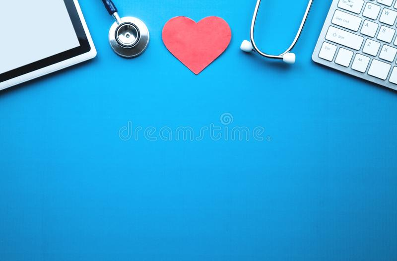 Tablet, stethoscope, red heart and computer keyboard on blue background. Medical concept stock image