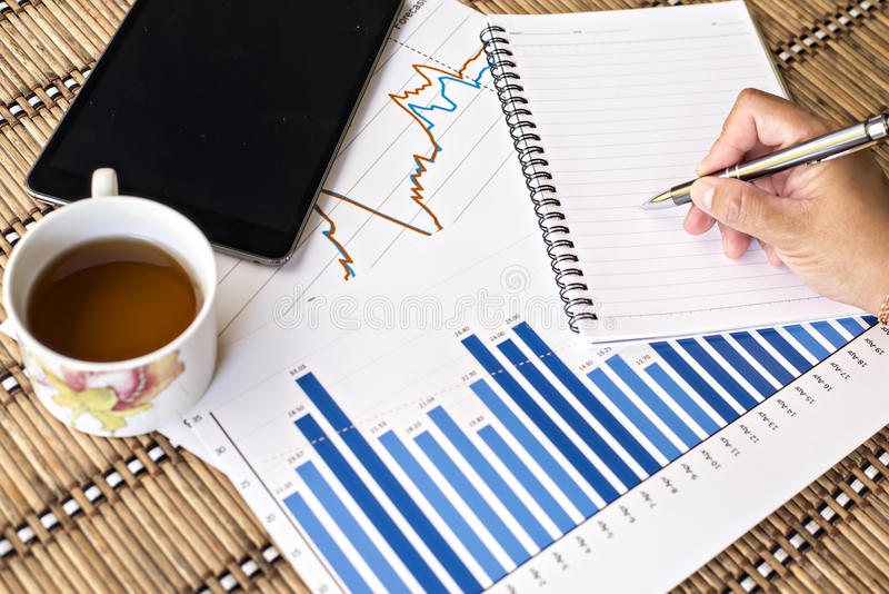 Tablet and tea cup with financial documents royalty free stock photos