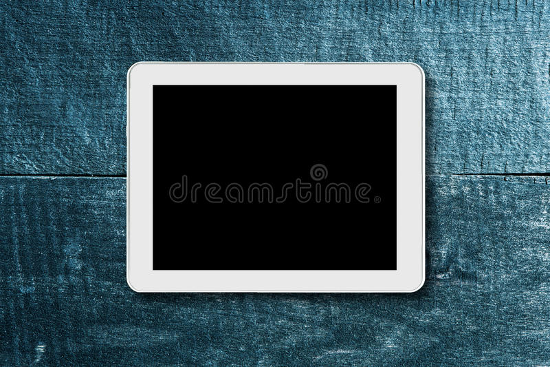 Tablet touch computer on a background of wood. stock photo