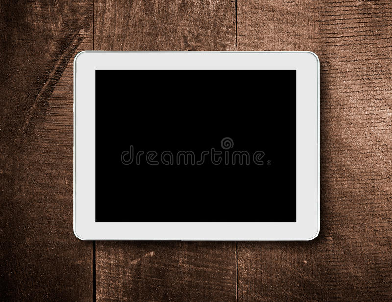 Tablet touch computer on a background of wood. royalty free stock photo