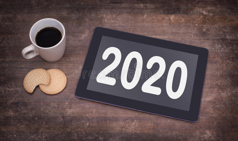 Tablet touch computer gadget on wooden table - 2020. Tablet touch computer gadget on wooden table, vintage look - 2020 stock photos