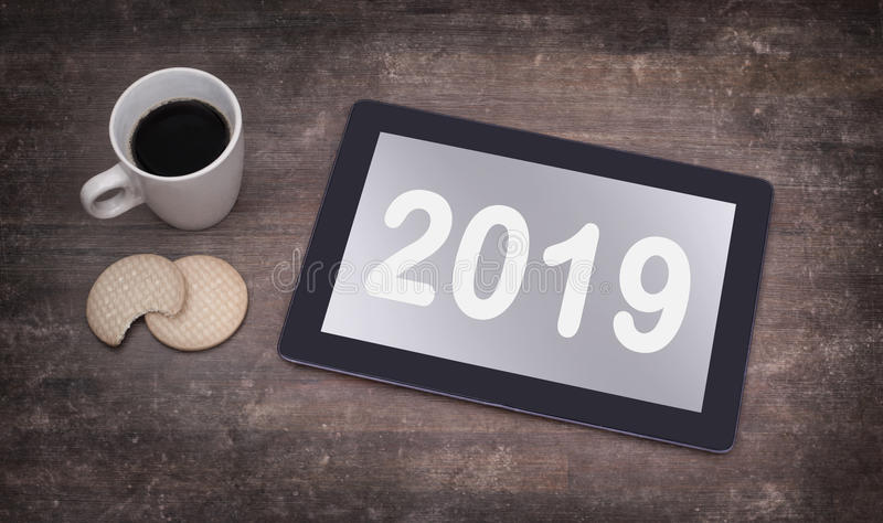 Tablet touch computer gadget on wooden table - 2019. Tablet touch computer gadget on wooden table, vintage look - 2019 royalty free stock photos