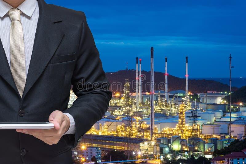 Tablet van de techniek de werkende greep met de krachtcentrale van de olieraffinaderij stock afbeeldingen