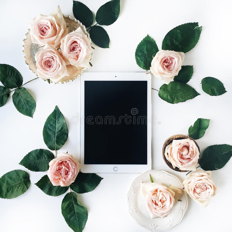 Tablet, vintage golden tray, retro plate and pink rose flower with green leaves on white background royalty free stock photography