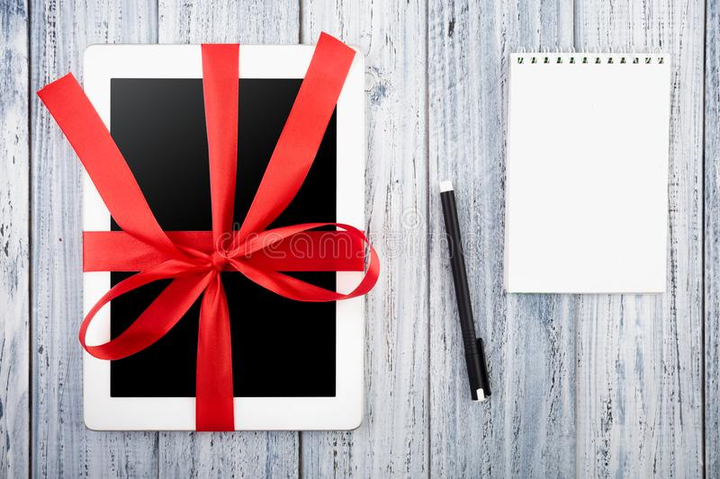 Tablet wrapped in red ribbon, paper notebook, pen on white vintage wooden background royalty free stock photos