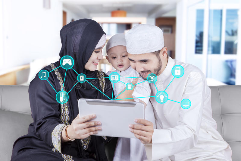 Tableta árabe del uso de la familia con el regulador casero elegante imágenes de archivo libres de regalías