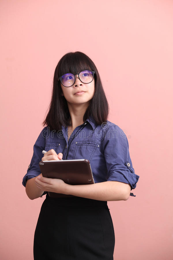 Tableta adolescente asiática de la escritura foto de archivo