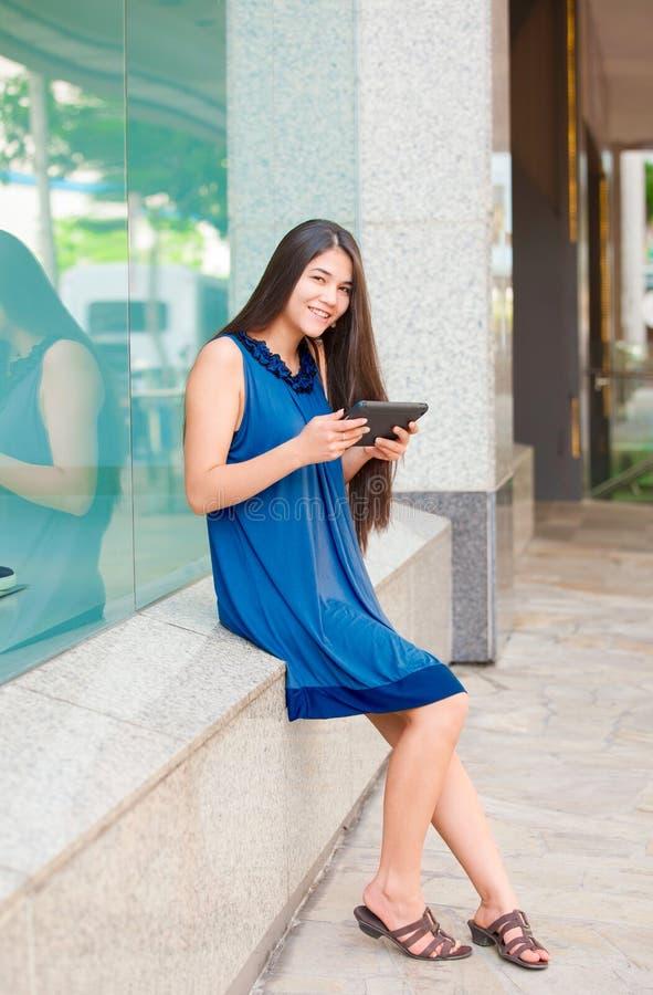 Tableta adolescente Biracial de la tenencia de la muchacha que se sienta fuera de ventana de tienda imagen de archivo libre de regalías