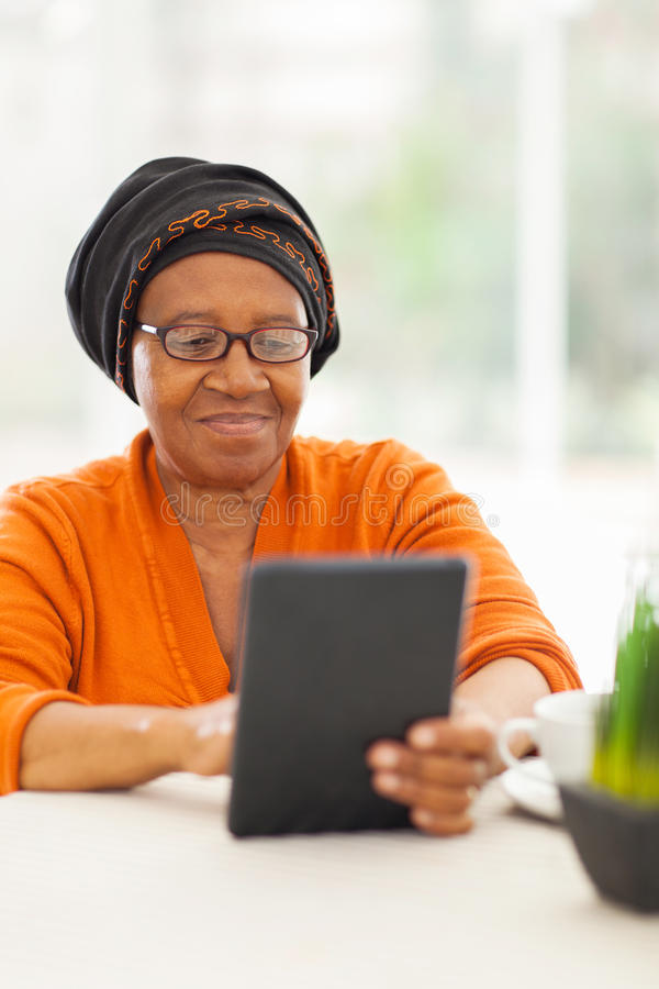 Tableta africana mayor de la mujer foto de archivo libre de regalías
