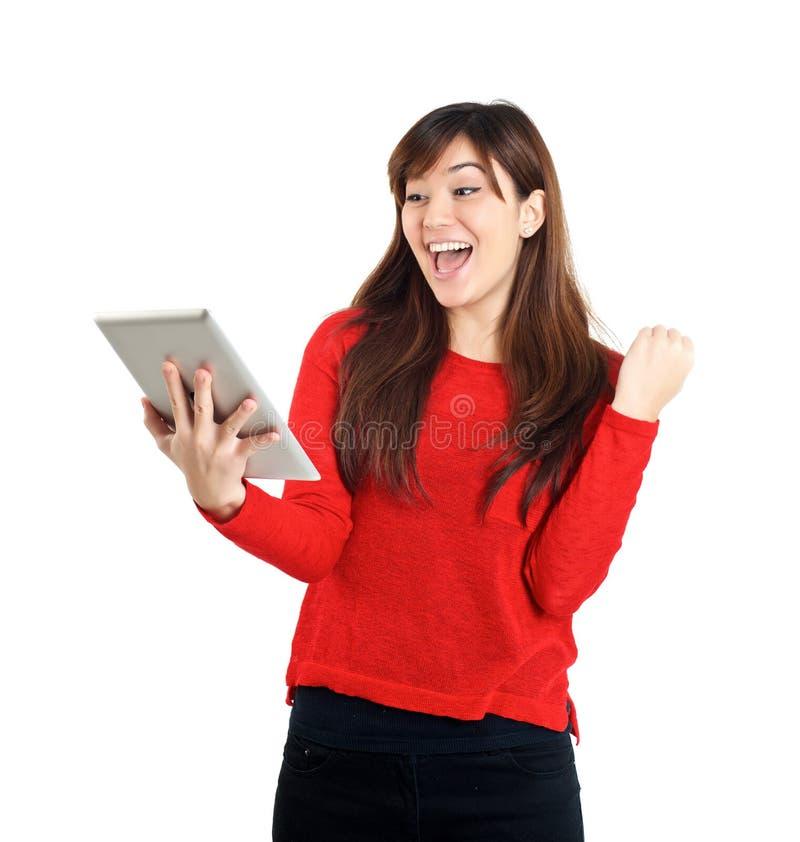 Tableta asiática de la tenencia de la muchacha con el puño de bombeo fotografía de archivo libre de regalías
